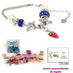 Pulsera con piedras blancas y azul electrico y un colgante de fresa